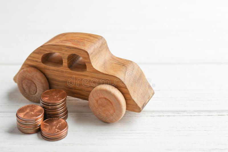 Car model and coins on wooden background. Space for text. Car model and coins on white wooden background. Space for text stock photography
