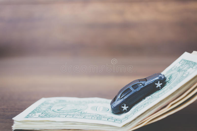 Car model on dollar banknotes on wooden background. Car model on dollar banknotes , cost of buying a car on wooden background royalty free stock photography