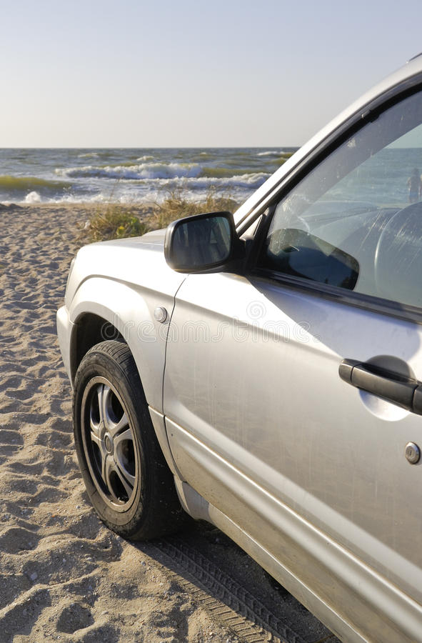 Car near the sea. Silver car stands on the beach royalty free stock photo