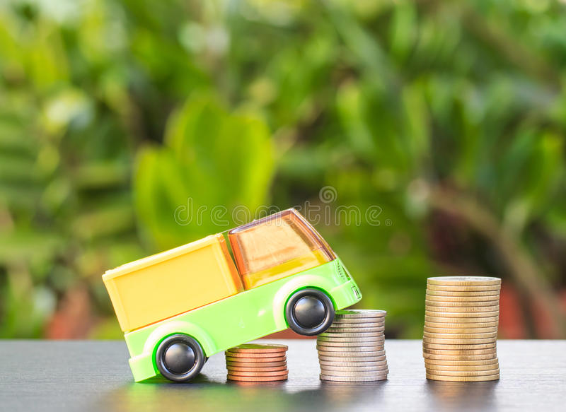 Car over a lot of stacked coins. Declining profits in the automobile and for car manufacturers stock photo