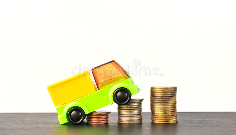 Car over a lot of stacked coins. Declining profits in the automobile and for car manufacturers royalty free stock photo