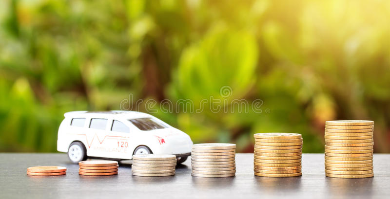 Car over a lot of stacked coins. Declining profits in the automobile and for car manufacturers royalty free stock images