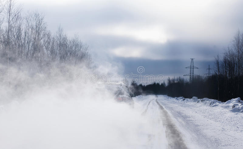 The car when overtaking has lifted a loop of snow dust. Poor visibility. Dangerous slick road. The car when overtaking has lifted a loop of snow dust. Poor stock photo