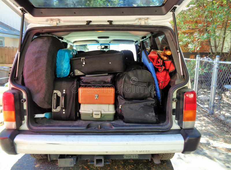 Car Packed for Vacation. An image of the rear of a car packed with suitcases and baggage ready to leave for a trip. The back hatch is open revealing various stock photo