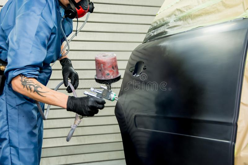 car painter paints the fender of a car royalty free stock images