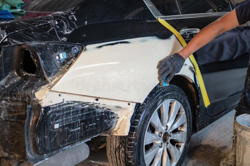 Car painting procedure at auto service store , Car accident at t. Repairing car body by puttying close up work after the accident by working sanding primer stock photos