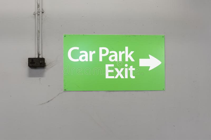Car park exit sign green white wall. Uk stock image