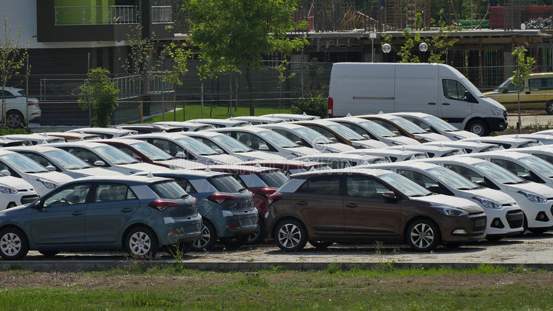 Car park. A long line of cars outdoors in the parking stock images