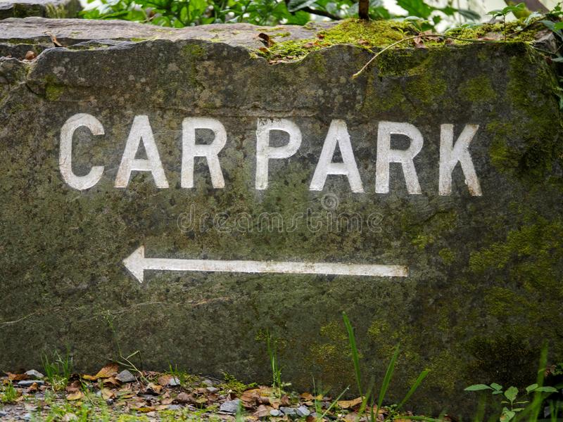 Car park sign on a stone with an arrow pointing to the left royalty free stock image