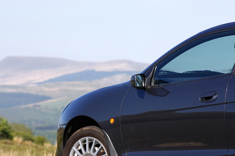 Car parked in the countryside. In front of hills stock photos