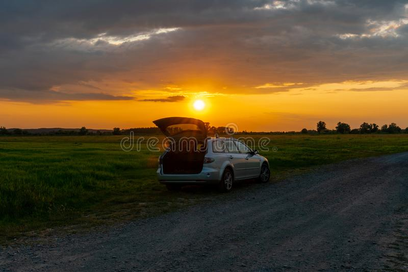 A car parked on a field at sunset in a rural landscape. In Guelpe, Brandenburg, Germany royalty free stock image