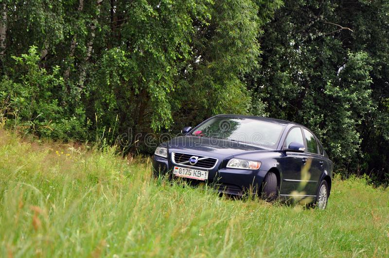 A car is parked on the grass outside the city. Luninets, Belarus - June 23, 2019: a car is parked on the grass outside the city stock photography