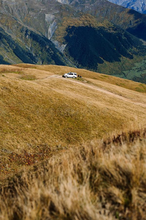 Car parked high in the mountains. People sitting on grass enjoying a breathtaking view of beautiful mountain tops on a sunny autumn day. Dangerous road trip to royalty free stock images