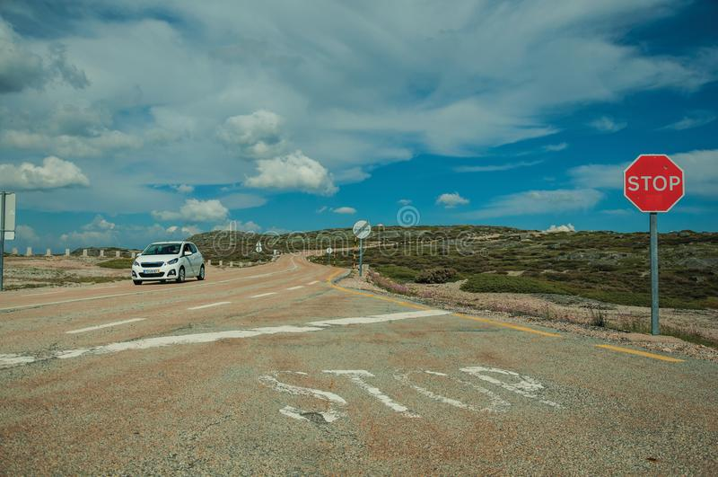 Car passing through road with STOP traffic sign. On rocky landscape and bush fields, at the highlands of Serra da Estrela. The highest mountain range in stock image
