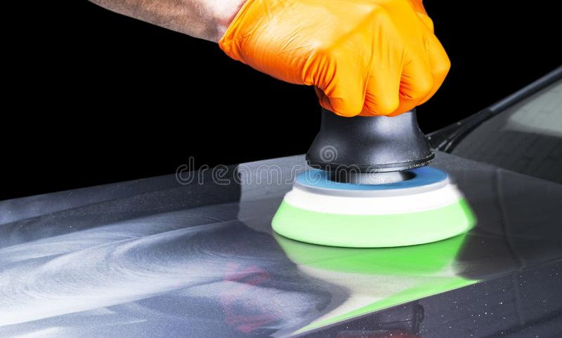 Car polish wax worker hands applying protective tape before polishing. Buffing and polishing car. Car detailing. Man holds a polis royalty free stock photo