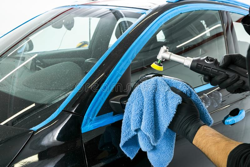 Car polish wax worker hands applying protective tape before polishing. Buffing and polishing car. Car detailing. Man holds a polis. Her in the hand and polishes stock image