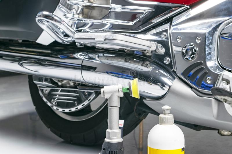 Car polish wax worker hands applying protective tape before polishing. Buffing and polishing motorcycle. Car detailing. Man holds. A polisher in the hand and royalty free stock images