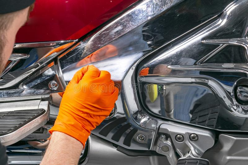Car polish wax worker hands applying protective tape before polishing. Buffing and polishing motorcycle. Car detailing. Man holds. A polisher in the hand and royalty free stock photos