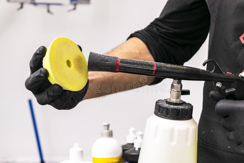 Car polish wax worker hands cleaning polishing sponge before polishing. Buffing and polishing car. Car detailing. Man holds a poli. Sher sponge in the hand stock photos