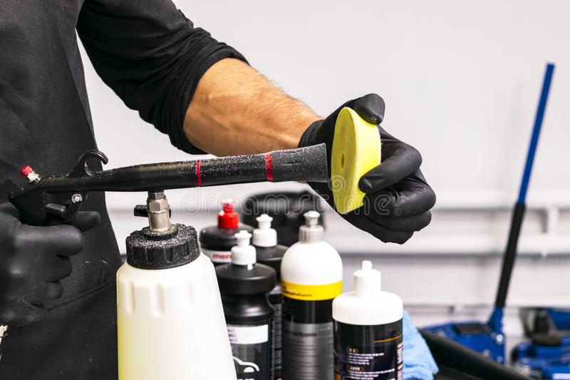 Car polish wax worker hands cleaning polishing sponge before polishing. Buffing and polishing car. Car detailing. Man holds a poli. Sher sponge in the hand royalty free stock images