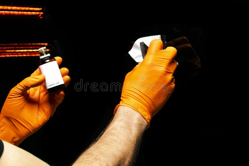 Car polish wax worker hands polishing car. Buffing and polishing vehicle with ceramic. Car detailing. Man holds a polisher in the royalty free stock photo