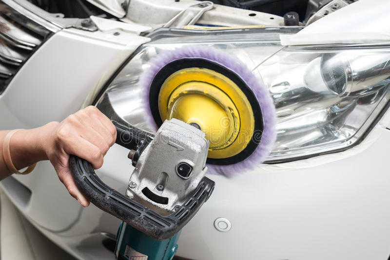 Car polishing series. Closeup of worker's hand polishing headlight royalty free stock photos
