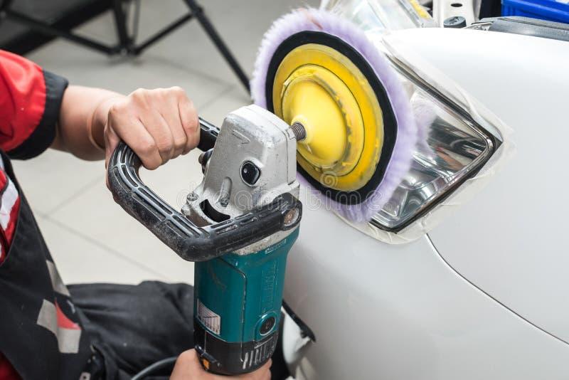 Car polishing series. Closeup of worker's hand polishing headlight royalty free stock photography