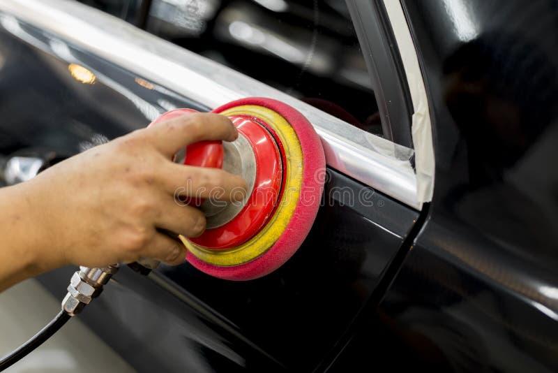 Car polishing series. Closeup of worker's hand using tool waxing black car hood in garage royalty free stock images
