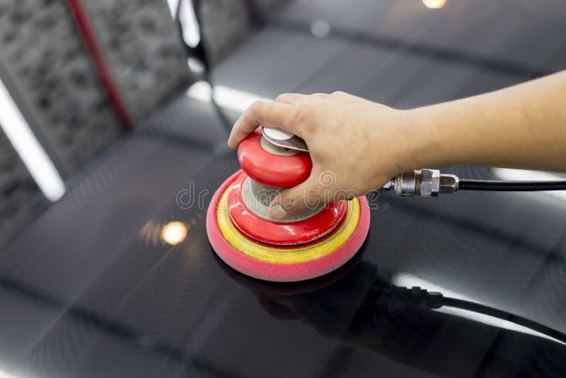 Car polishing series. Closeup of worker's hand using tool waxing black car hood in garage stock photo