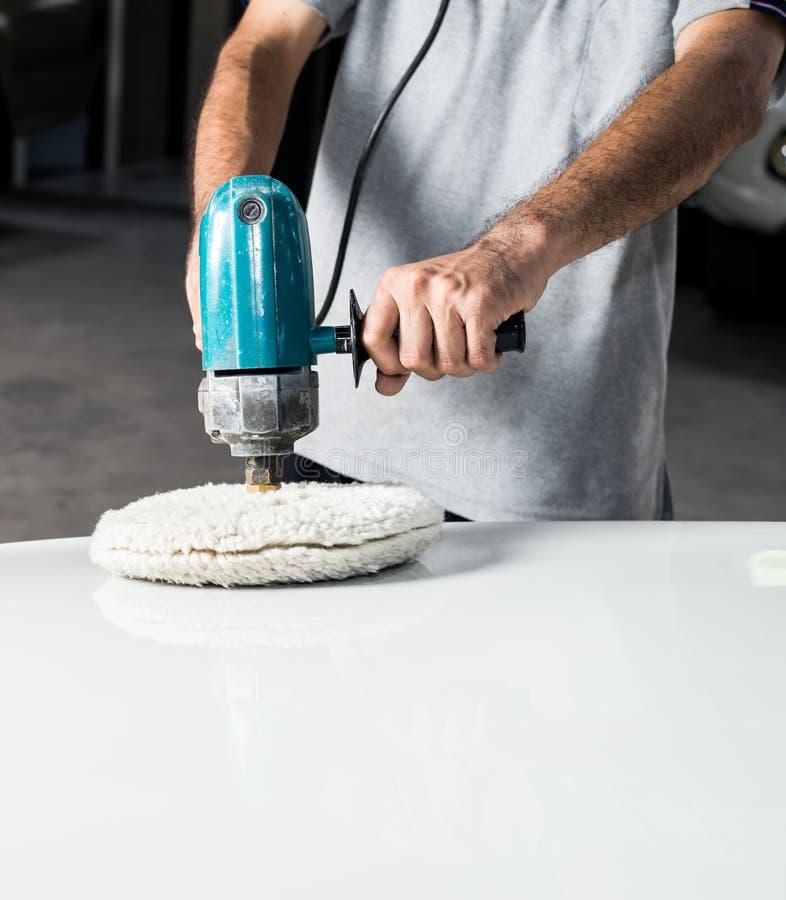 Car polishing series. Closeup of worker's hand waxing white car royalty free stock photos