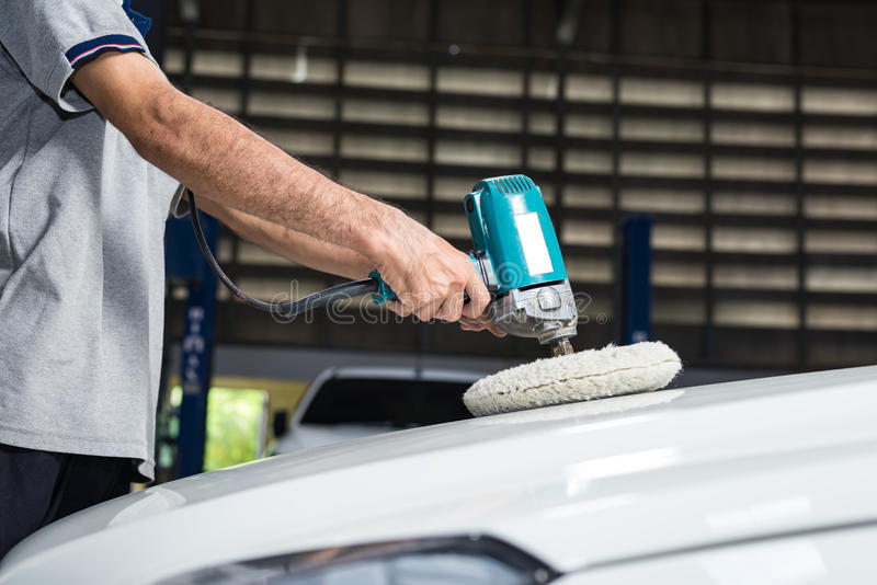 Car polishing series. Closeup of worker's hand waxing white car stock images