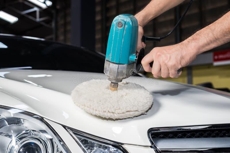 Car polishing series. Closeup of worker's hand waxing white car stock image