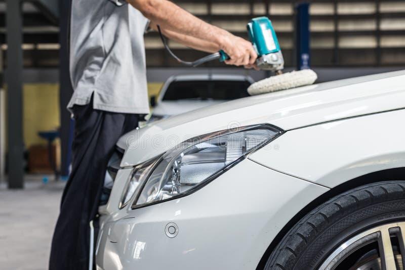 Car polishing series. Closeup of worker's hand waxing white car stock photography