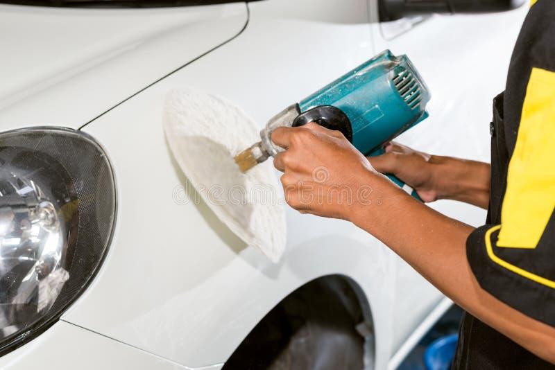 Car polishing series. Closeup of worker's hand waxing white car stock photo