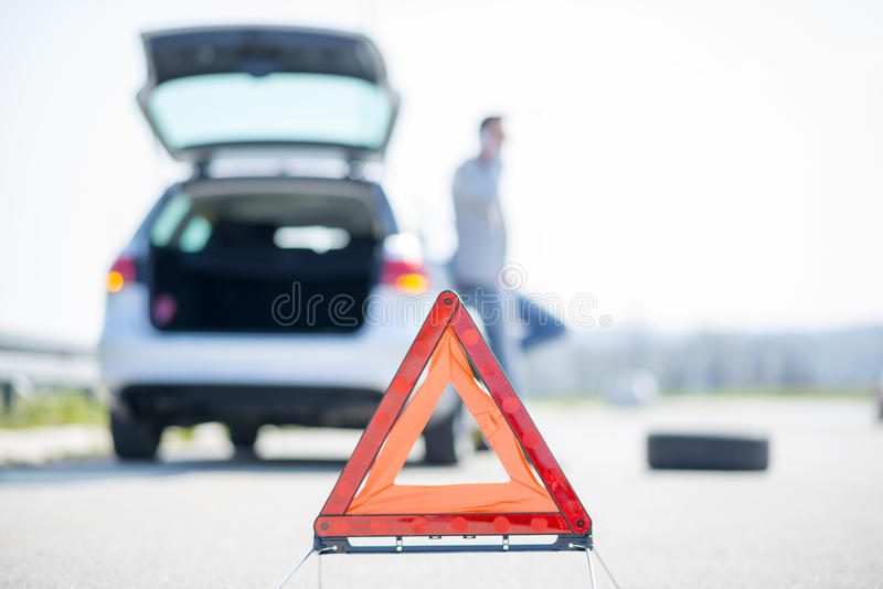 Car problems, red warning triangle!. A young man with a silver car that broke down on the road.He has set up a warning triangle.He is waiting for the technician stock photos