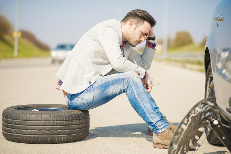 Car problems. A young man with a silver car that broke down on the road.He is sitting near car with punctured tire stock photo