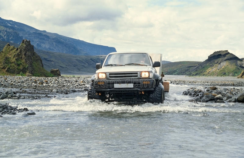 Car pulling trailer and crossing river in Iceland. 4x4 Pick-up truck crossing river with splashing water. Travel concept for off-road adventure and fun in stock images