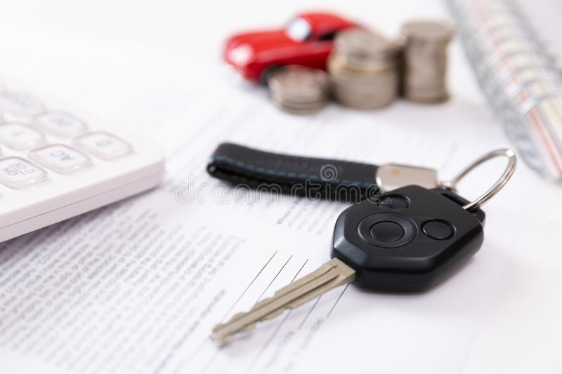 Car purchase concept. Car keys, calculator, toy car, coins and purchase contract. In a natural light royalty free stock photo