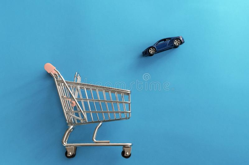 Car purchase concept. Toy blue automobile falling to shopping trolley cart on blue background. Buying new car. Online. Shopping. Digital car buying stock images