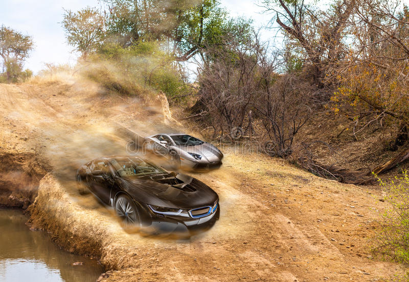 Car race. On dirty road between a BMW i8 and Lamborghini Aventador stock images