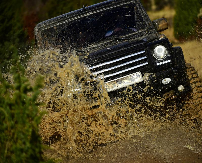 Car racing in autumn forest. Auto racing on fall nature background. Off road vehicle or SUV crossing puddle with dirt. Splash. Competition, energy and royalty free stock photography