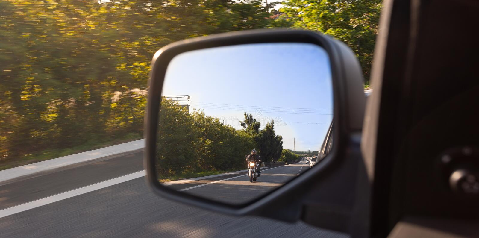 Car rear view mirror with the image of a biker approaching to overtake royalty free stock images