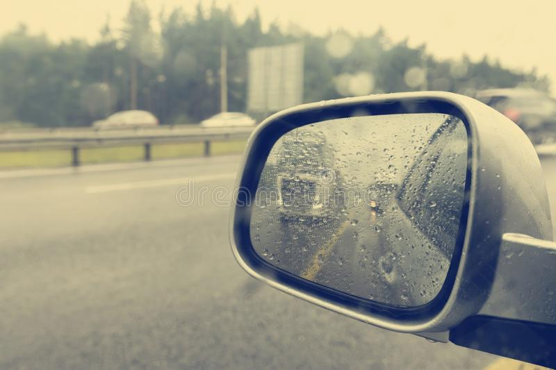 Car rear view mirror in the rain.  royalty free stock image