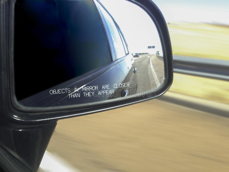 Car rear view mirror warning message in motion. Car rearview mirror with warning Objects in mirror are closer than they appear. Blurred motion view of the road stock photos