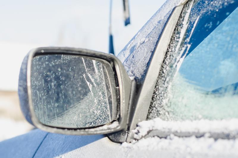 Car rearview mirror covered with white frost and snow on a sunny winter day royalty free stock photo