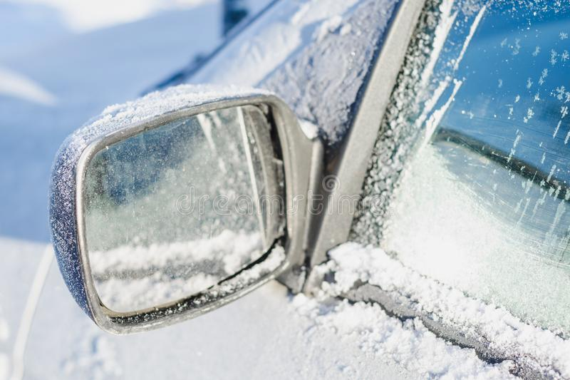 Car rearview mirror covered with white frost and snow on a sunny winter day stock photo