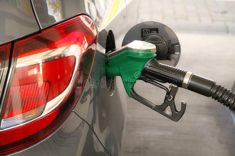 Gasoline car refueling at the petrol station. Concept for use of fossil fuels gasoline, diesel in combustion engines stock image