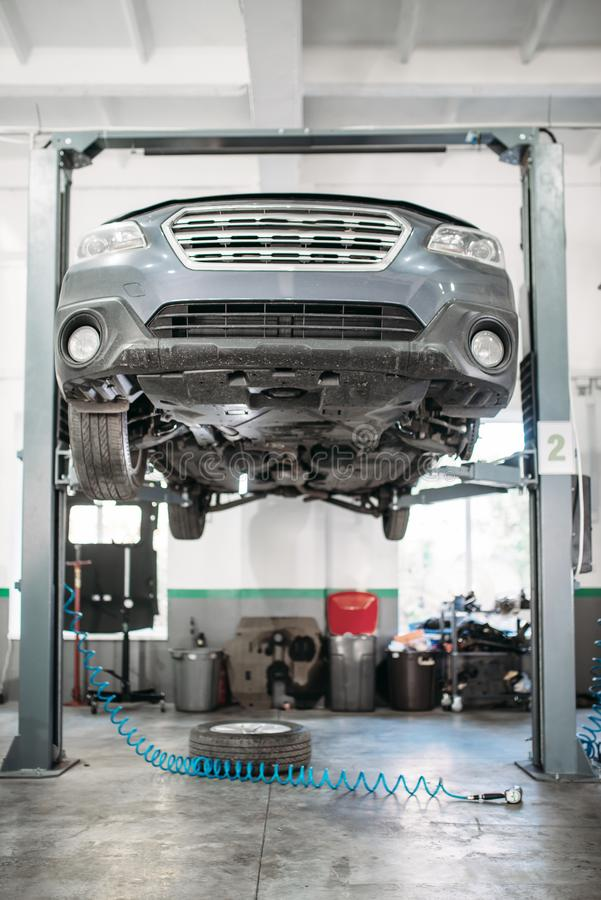 Car with removed wheel on the lift, nobody. Automobile repair, vehicle maintenance, tire service royalty free stock photos