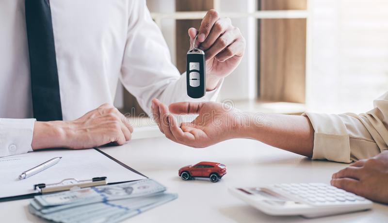 Car rent agent manager holding key of new car giving to woman client after signing good deal agreement contract, renting stock photos