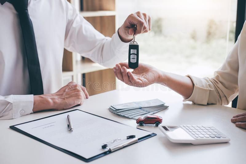 Car rent agent manager holding key of new car giving to woman client after signing good deal agreement contract, renting royalty free stock image